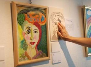 牆上一幅粉彩畫作旁邊有一幅觸感圖;有一隻手正觸摸觸感圖上的黑色線條和圖紋