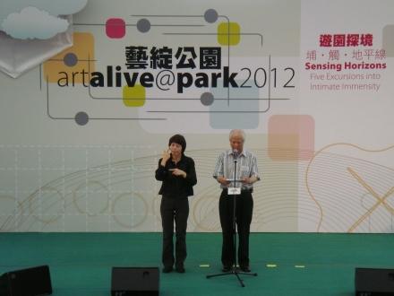 台上的嘉賓正在致詞,旁邊有一位全身穿黑衣的手語傳譯。