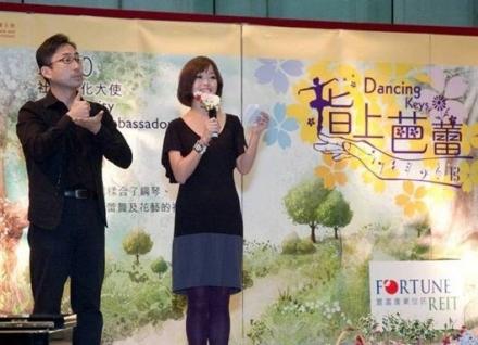 活動佈景板前有一位司儀,旁邊為一位全身穿黑衣的手語傳譯。