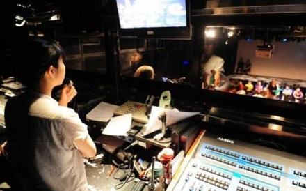 口述影像員拿著咪高峰從控制室望向舞台,舞台有穿著不同顏色衣服的演員一字排開,坐在地上。