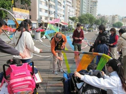放置於室外的藝術品,導賞員帶領參加者欣賞作品透射不同顏色的光線,部份參加者坐著輪椅。