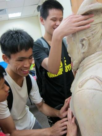 三位參加者正透過觸摸兵馬俑的複製模型了解它的外形和結構。