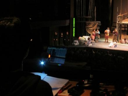 口述影像員從控制室望著舞台,舞台左方有三位劇場視形傳譯員,旁邊有顯示通達字幕的字幕機。