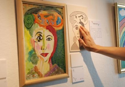牆上一幅油畫作品,作品右邊是相應的觸感圖,有一個人正伸手摸觸感圖凸起的線條。