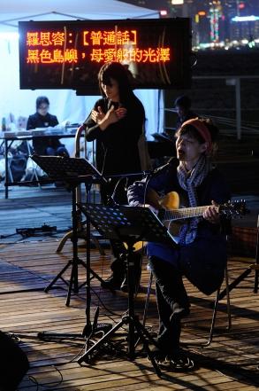 歌手自彈自唱,旁邊的劇場視形傳譯員身後有通達字幕。