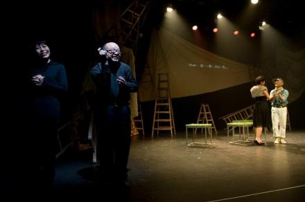 相片左方兩位劇場視形傳譯員面帶笑容,與右方舞台的兩位演員一同演繹角色;演員後方有通達字幕的投影。